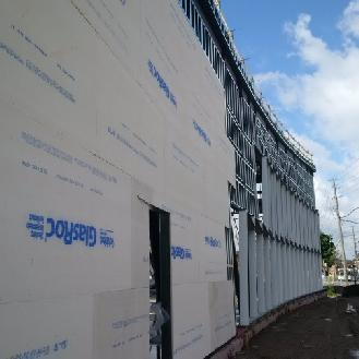Exterior sheathing installation is underway along the north elevation.