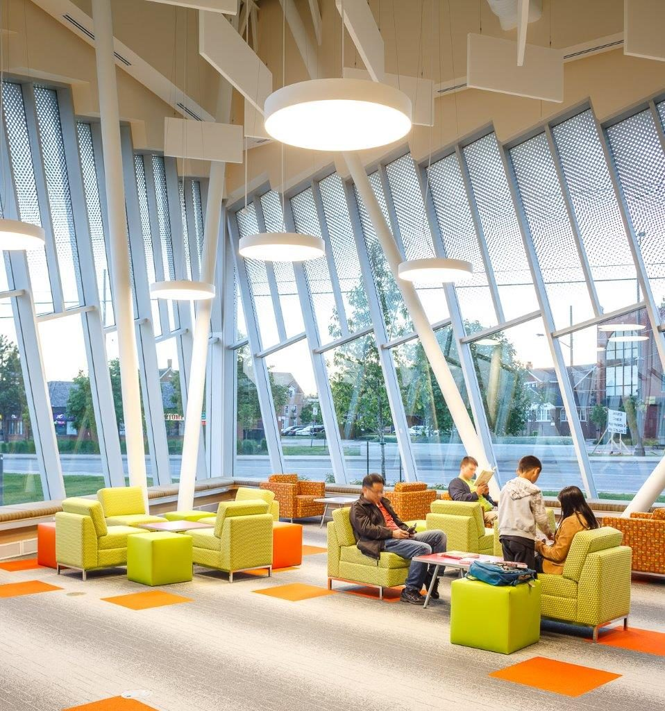 "High ceilings with rectangular baffles and circular lighting give ""shape"" to a comfortable area to read."