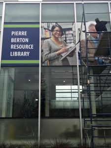 Placing the colourful film on Pierre Berton Resource Library's windows.