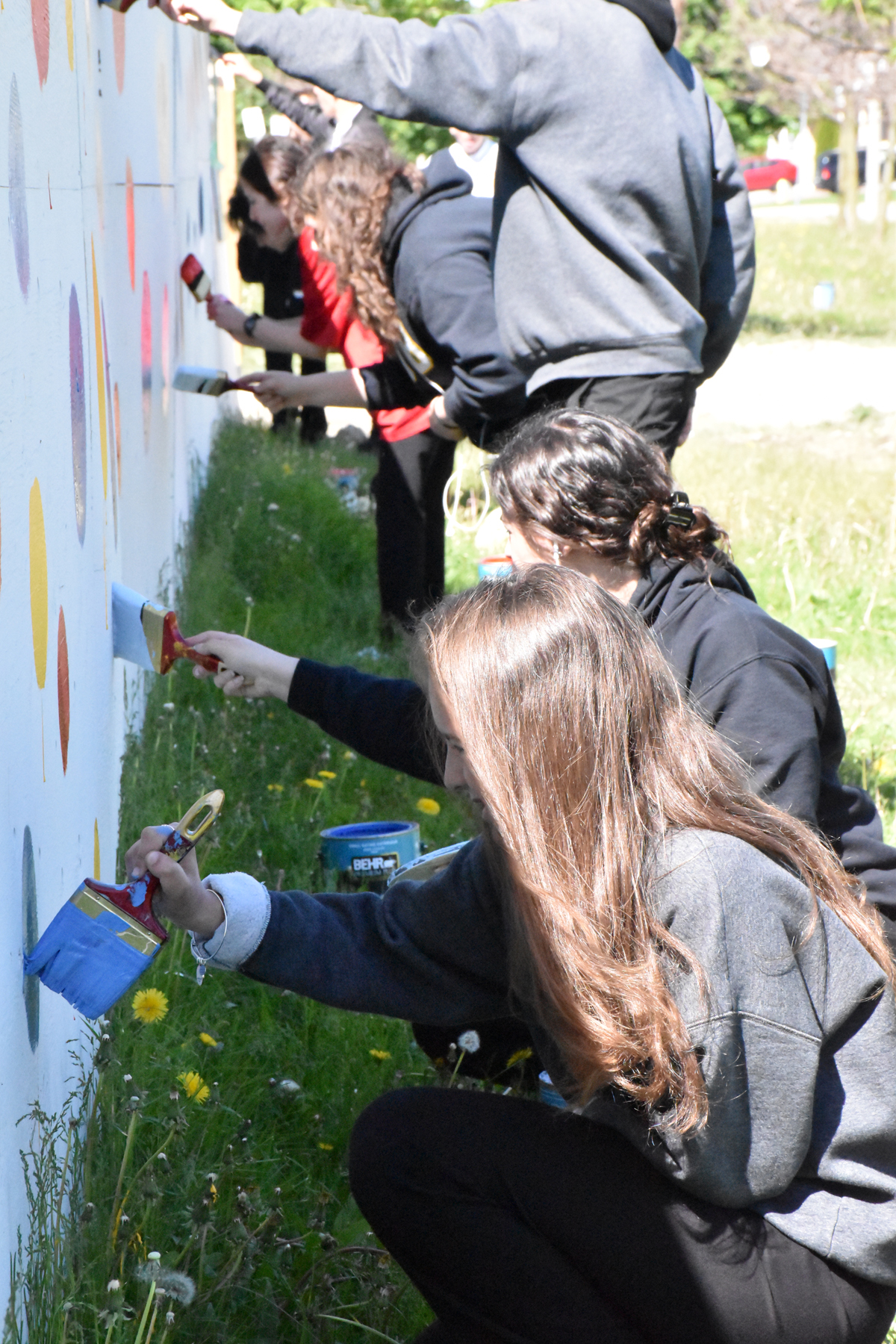 Students painting VVSL hoarding fence