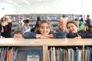 Girls leaning on book shelves